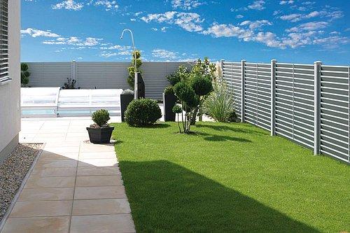 Moderner Sichtschutzzaun aus Aluminium in grau umzäunt einen Garten mit Pool