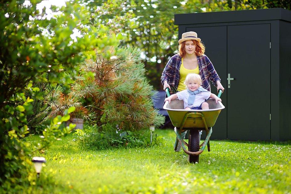 Moderne Gartenhütte aus Stahl in anthrazit steht im Garten, während davor eine Mutter mit ihrem Kind spielt