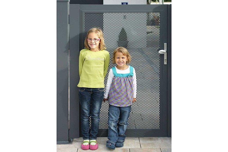 zwei Mädchen lehnen an einer Lochblechtür in der Einfahrt zum Haus