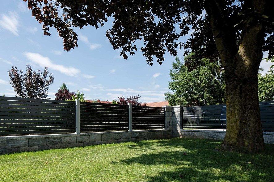 moderner Lattenzaun mit Querlatten in anthrazit - Blick vom Garten unter einem Baum