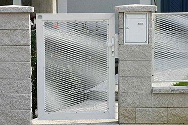 Gartentür mit Lochblech aus Aluminium in weiß an einer Mauer angebracht.