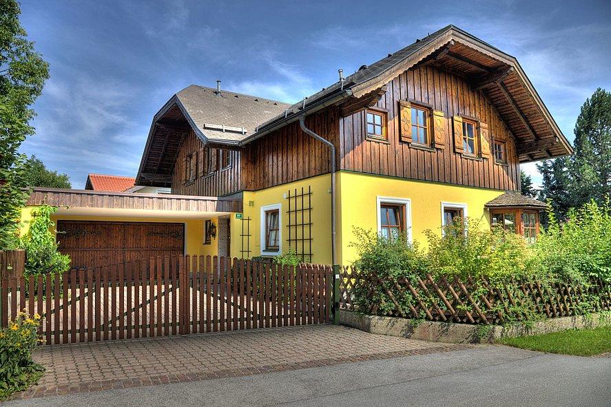 Doppelflügeltor aus Latten in Holzoptim braun integriert in Lattenzaun zur Hofeinfahrt ein großen Hauses