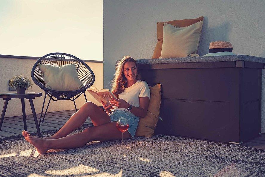 Gartenbox aus Stahl in anthrazit auf dem Balkon, davor sitzt eine Frau und liest ein Buch