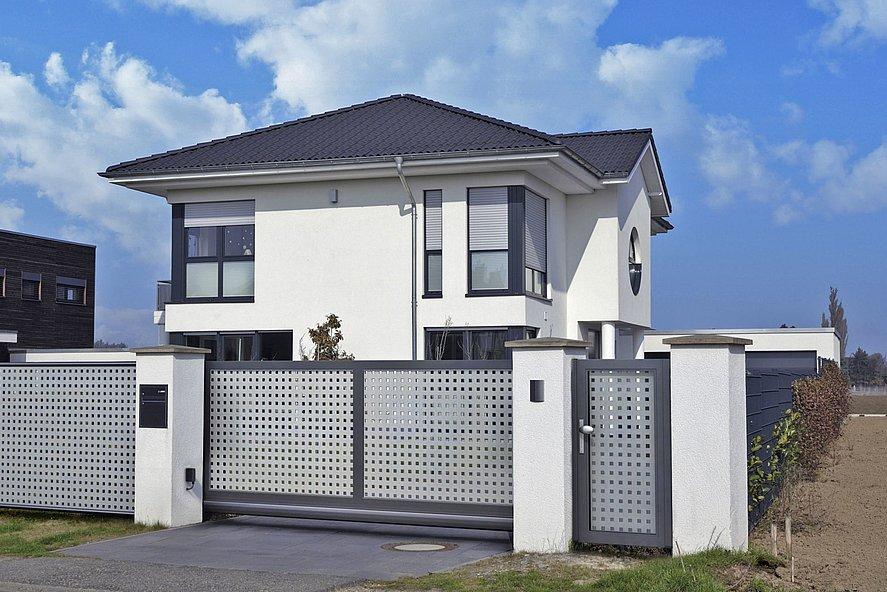 elegantes Schiebetor und Gartentür zweifärbig in grau und dunkelgrau vor alleinstehendem Haus