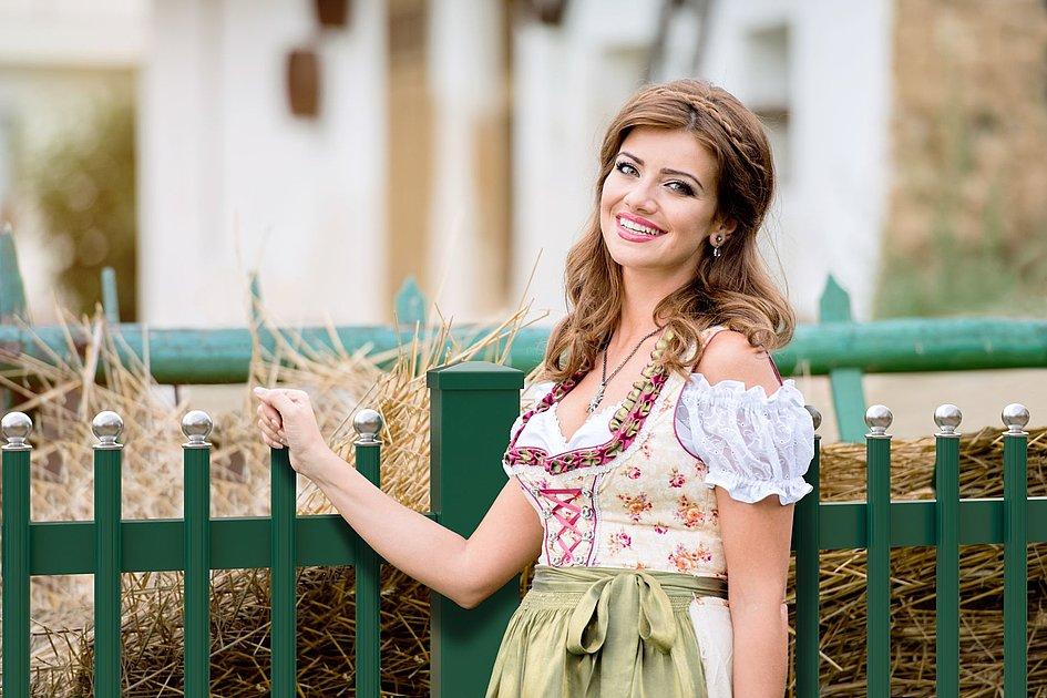 junge Frau in Dirndl steht vor grünem Palisadenzaun mit silbernen Zaunkappen in Kugelform