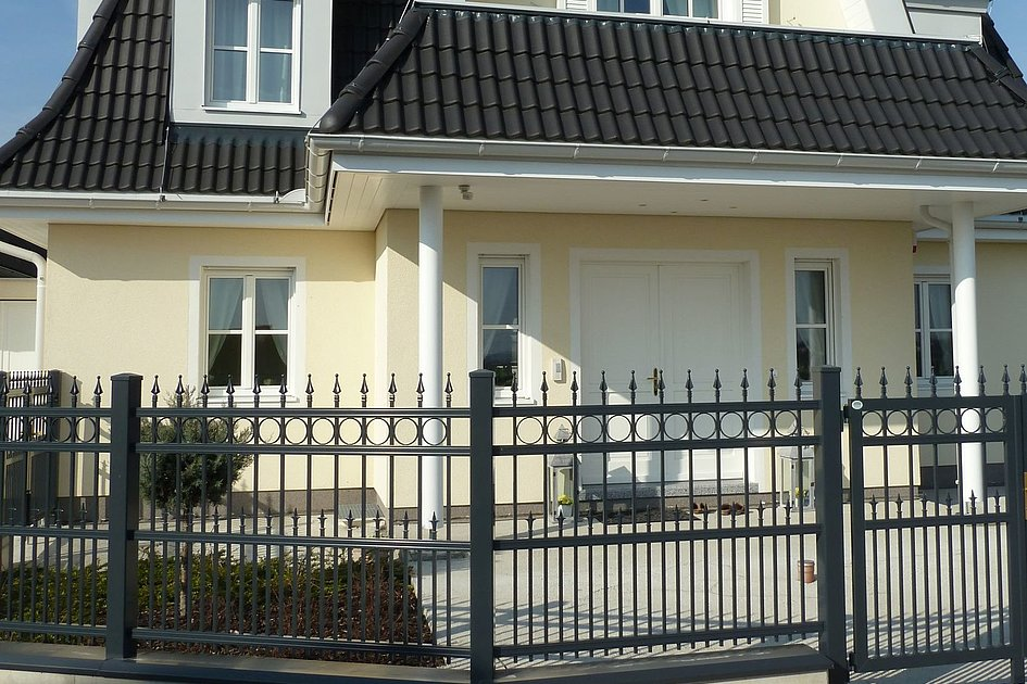 Aluminiumzaun in Kunstschmiedeoptik vor Haus mit Einganssäulen