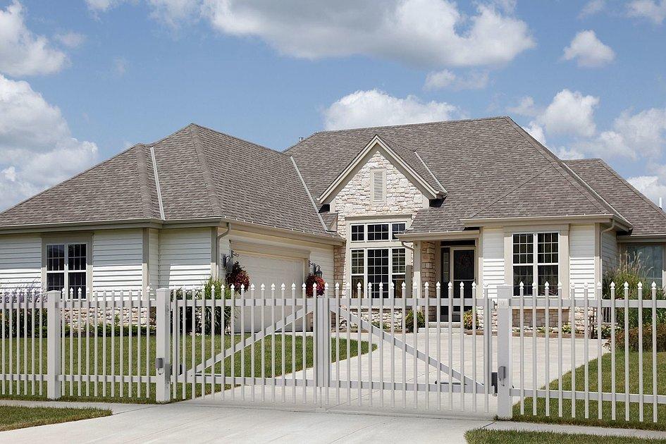 Zweiflügeltor mit Palisaden in verschiedenen Farben vor klassischer Familienvilla