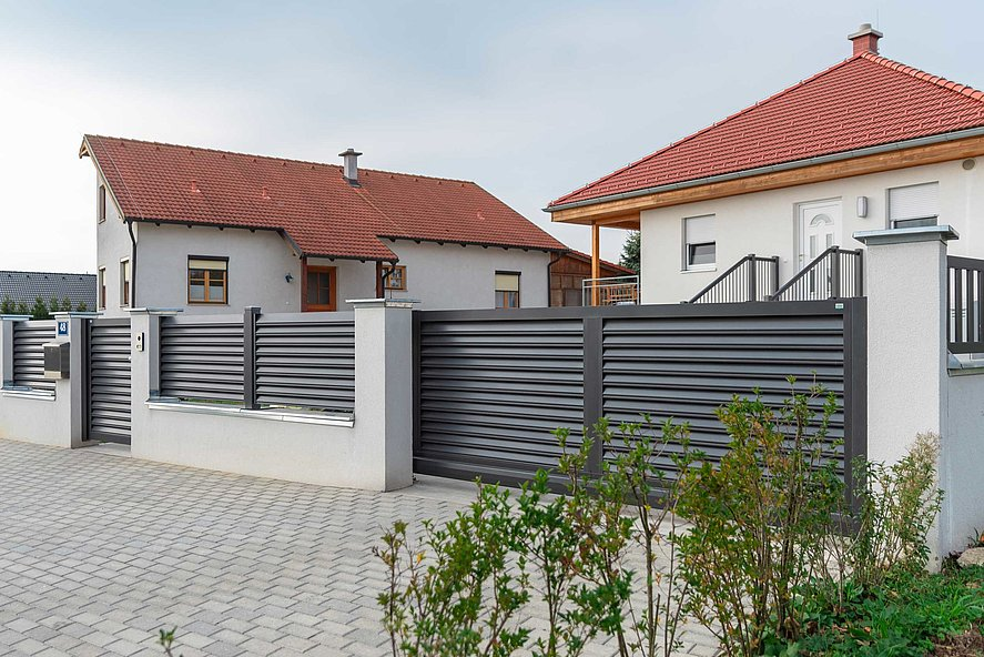 Zaun mit Lamellen als Sichtschutz in grau und Gartentor,sowie Gartentür umzäunt eine moderne Hausanlage