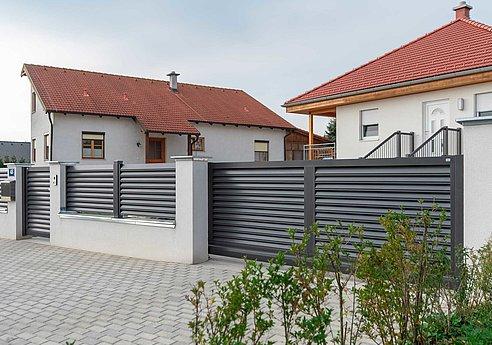 Schiebetor elektrisch mit Lamellen als Sichtschutz in grau und Gartentor,sowie Gartentür umzäunt eine moderne Hausanlage