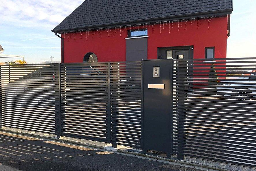 Briefkastensäule zu modernem Zaun, beide anthrazit, vor freistehendem Haus mit roter Fassade
