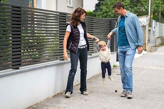 Moderner Aluminiumzaun mit Querlatten aus Aluminium auf einer Steinmauer, davor spaziert eine Familie