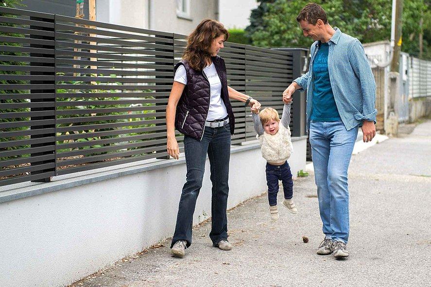 moderner Lattenzaun in anthrazit auf weißem Mauersockel mit einer jungen modernen Familie davor