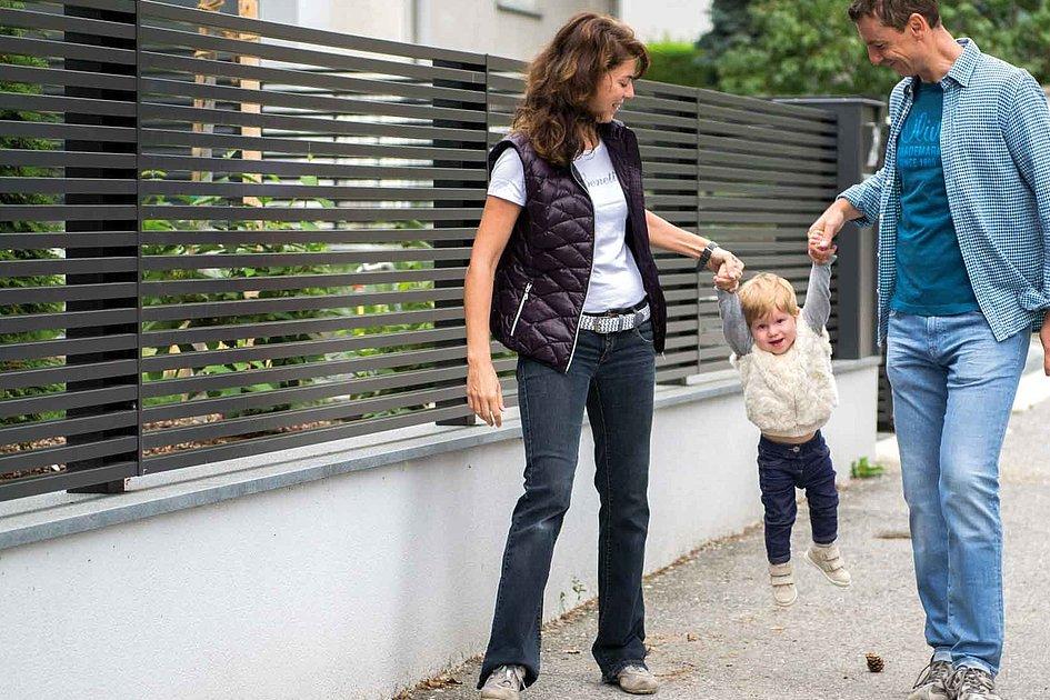 Familie mit Kind vor modernem Gartenzaun mit horizontalen Latten in anthrazit