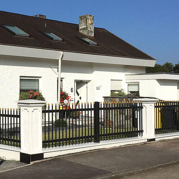 Palisadenzaun mit schwarzen Rundstäben und goldenen Zwiebelkappen umzäunt ein klassisches Einfamilienhaus