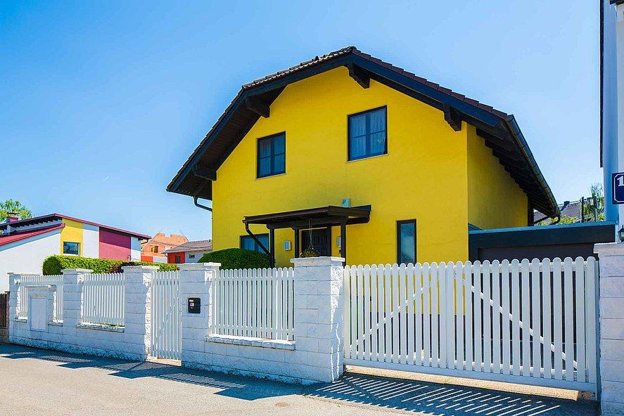 Doppelflügeltor und Gartentor in weiß mit Latten aus Aluminium als Einfahrtstor zu großem gelben Haus