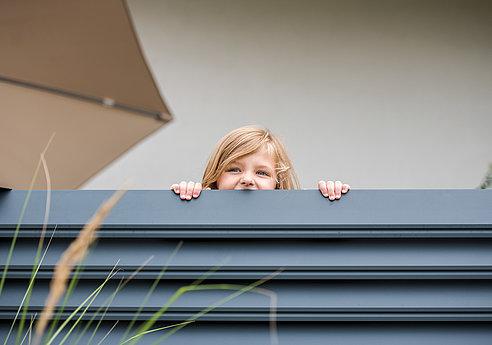 Kind schaut über einen Aluminiumzaun mit Querlatten in anthrazit