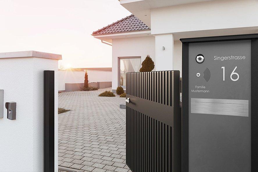 Briefkastensäule in grau neben moderner GArtentür aus Aluminium Latten, offen zur Einfahrt einer Villa