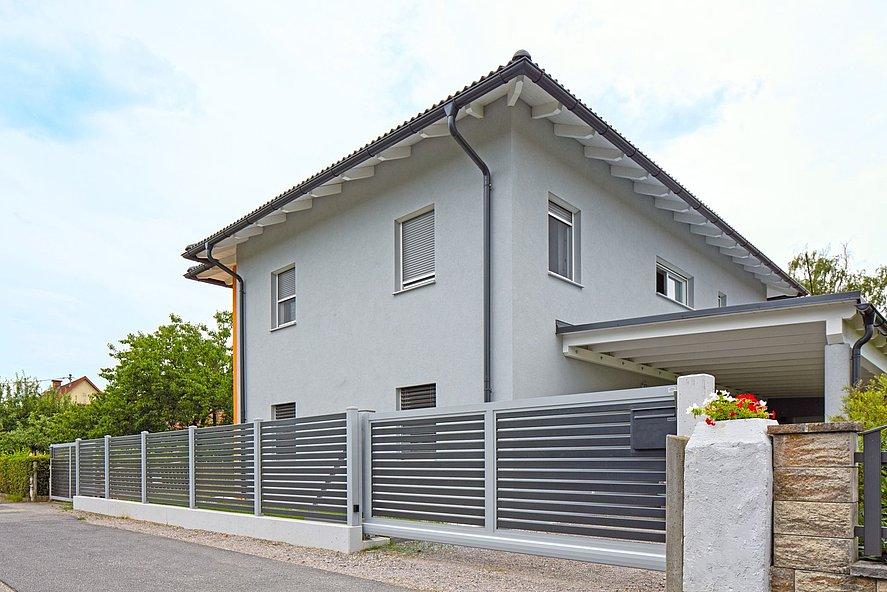 Aluzaun und Schiebetor mit Querlatten in modernem Designvor Einfamilienhaus der 2000er Jahre