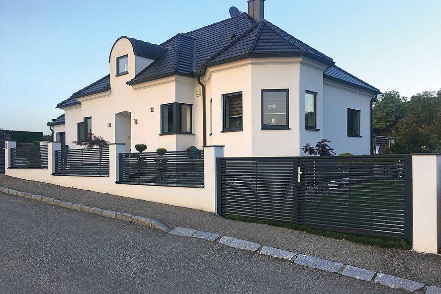 Lattenzaun mit Querlatten und Doppelflügeltor vor großem Einfamilienhaus am Hang