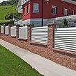 weißer Gartenzaun mit Lamellen auf Mauersockkel aus Backsteinen umzäunt ein Appartmenthaus in den Bergen