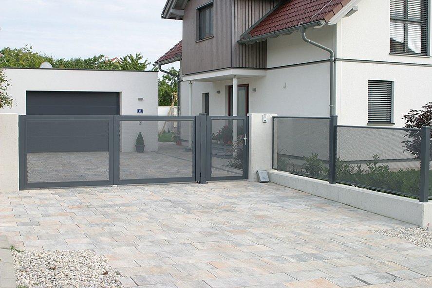 elektrische Doppelflügeltor und Gartenzaun mit Lochblech in grau vor großem Einfamilienhaus mit Garage