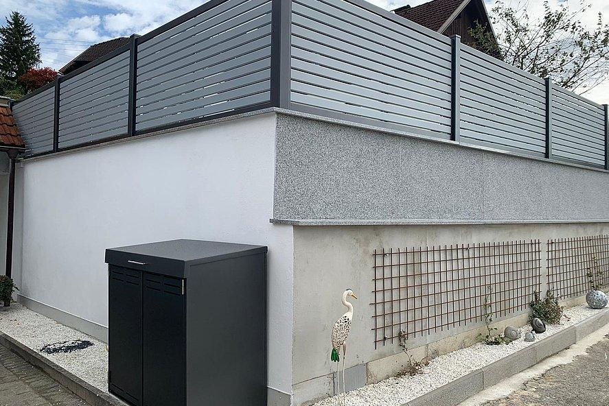 Mülltonnenbox für zwei Tonnen in anthrazit und Gartenzaun Modell TESLA aus Aluminium in grau im Hintergrund