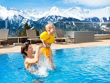 Gartenbox in silber auf Terrasse mit Pool und Glasgeländer. Mutter spielt mit Kind