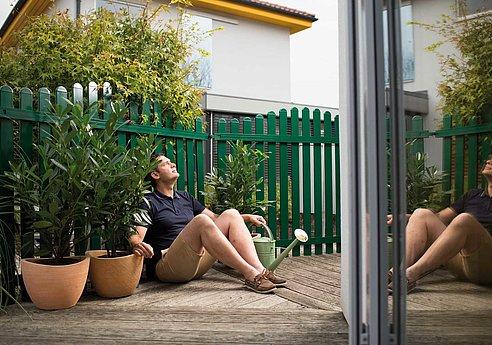 Mann sitzt nach getaner Arbeit vor einem grünen Lattenzaun aus Aluminium und schaut zufrieden in die Ferne