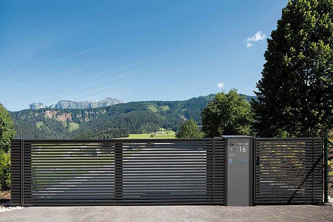 Eine lange Hauseinfahrt wird abgegrenzt durch ein modernes Flügeltor mit integrierter Briefkastensäule aus Aluminium in anthrazit