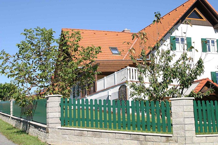 Lattenzaun aus Aluminium in grün vor weißem Bauernhaus mit Garten