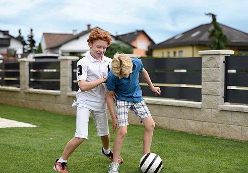 Zwei Buben spielen Fußball vor einem Aluminiumzaun mit breiten Querlatten in anthrazit