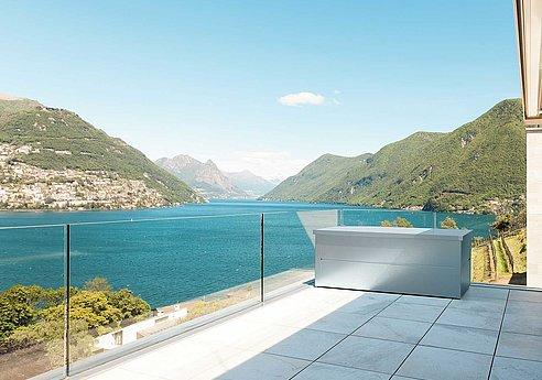 Moderne Gartenbox aus hochwertigem Stahl steht auf einem Balkon mit Blick auf einen See