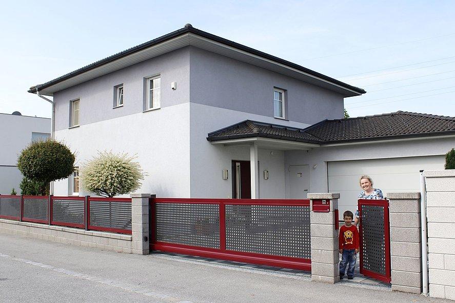Gartenzaun in rot mit dunkelgrau aus Lochblech mit Schiebetor und Gartentür aus der ein kleiner Junge kommt - dahinter ein großes Einfamilienhaus