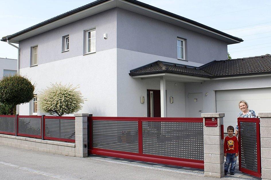 Schiebetor aus Lochblech mit verschiedenen Farben vor Einfamilienhaus in Siedlung