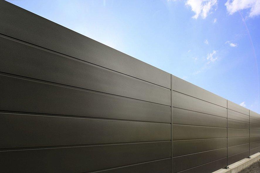 Nahaufnahme eines modernen Sichtschutzzauns mit ganzen Platten aus Aluminium in schwarz