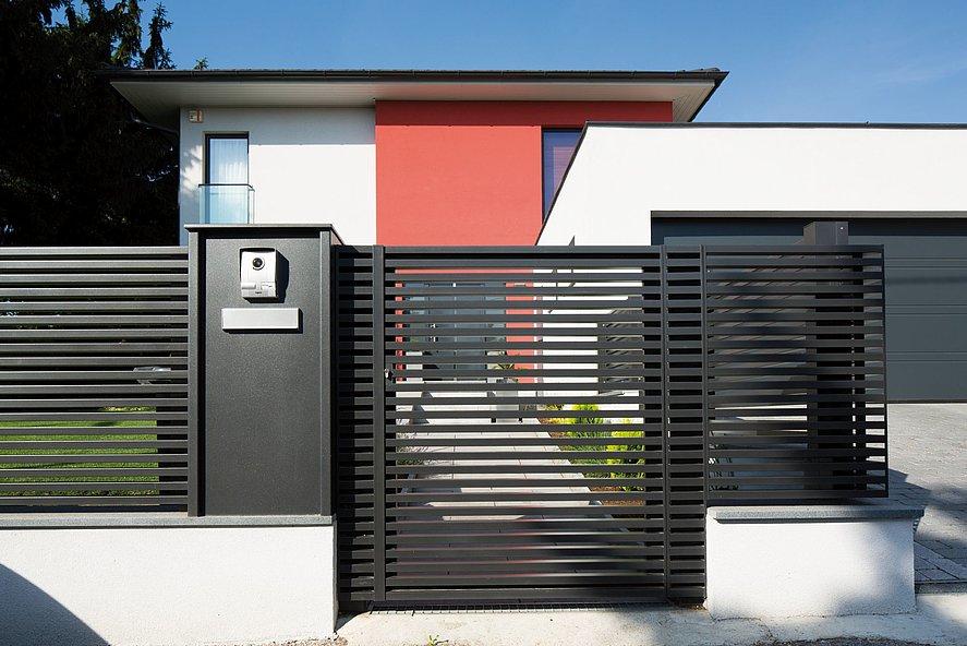 Gartentür mit modernen Querlatten in anthrazit als Eingang zu modernem Einfamilienhaus