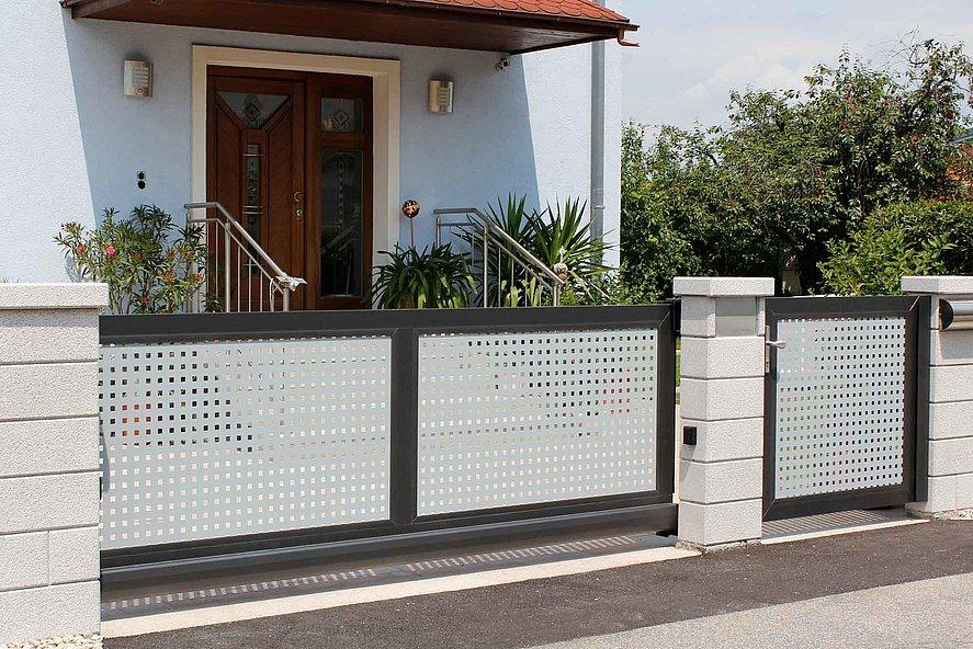 elektrisches Schiebetor und Gartentür mit Lochblech als Sichtschutz zur Hauseinfahrt