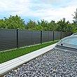 Blick vom überdachten Pool im Garten auf modernen Gartenzaun mit Querlatten aus Aluminium und Sichtschutz