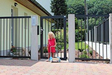 Gartentür mit Stäben aus Aluminium begrenzt einen Garten, im Vordergrund steht ein kleines Mädchen