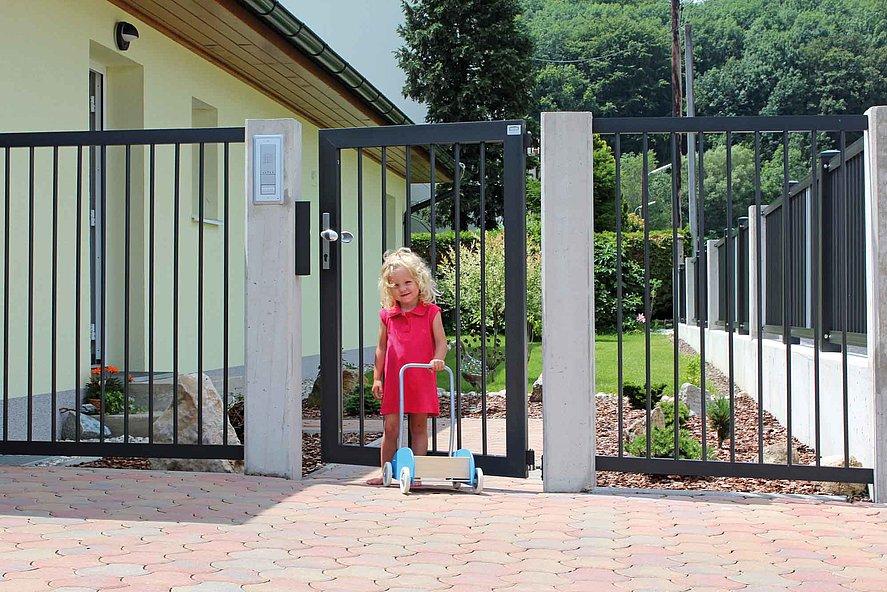 Gartentür in anthrazit zum Stabzaun mit kleinem Mädchen davor in gepflasterter Hofeinfahrt