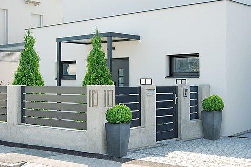 Moderner Gartenzaun mit Querlatten aus Aluminium in anthrazit begrenzt einen Hauseingang