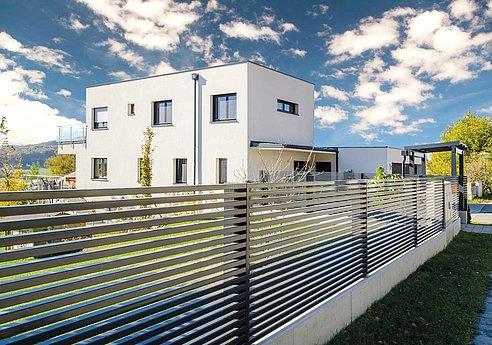 moderner Gartenzaun mit Querlatten in anthrazit vor modernem Architektenhaus