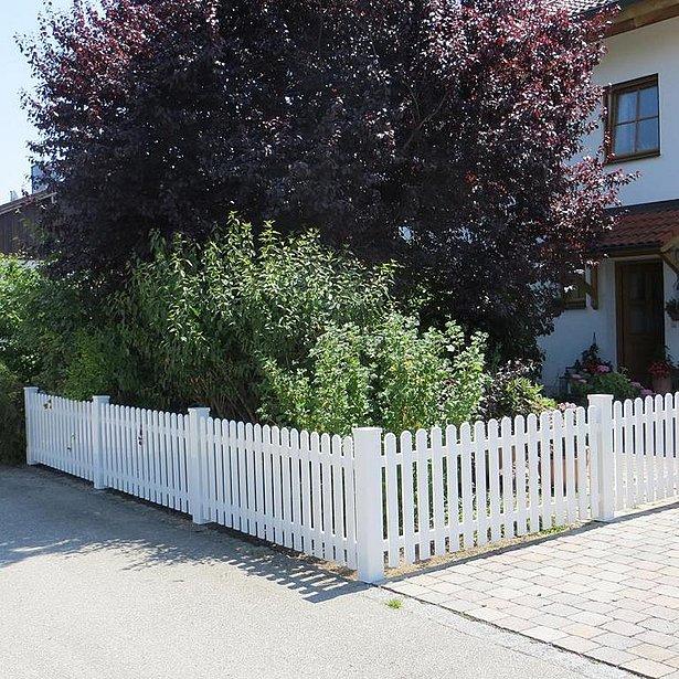 weißer Lattenzaun aus Aluminium umzäunt Vorgarten eines Einfamiliehauses