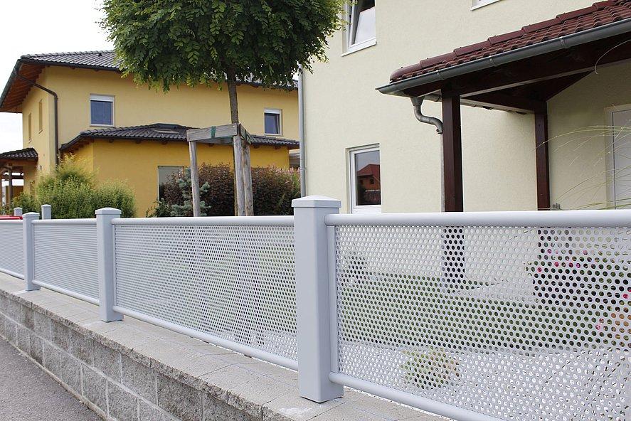 Nahaufnahme weißer Gartenzaunn mit Lochblech als Sichtschutz in einer Wohnsiedlung