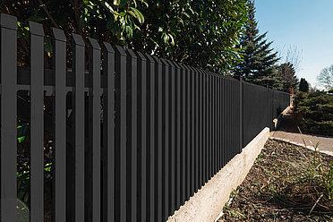 Gartenzaun aus Aluminium von Super-Zaun mit Latten und Schrägkappen in anthrazit auf einer Mauer montiert