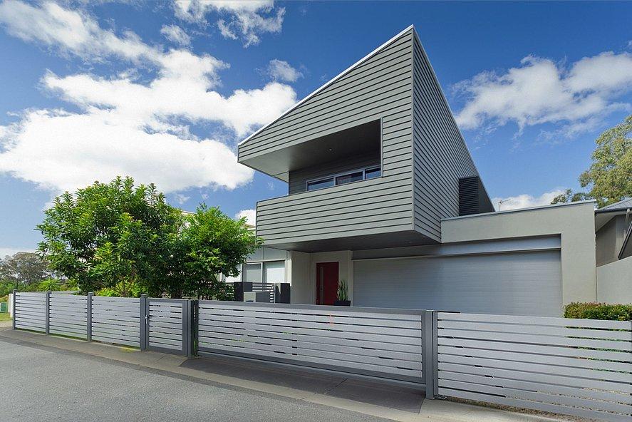 moderner Zaun aus Aluminium mit elektrischem Schiebetor vor einem Designhaus
