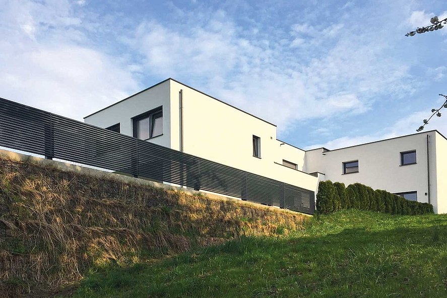moderner Lattenzaun auf Steinmauer umrahmt modernes Haus in kubischer Struktur