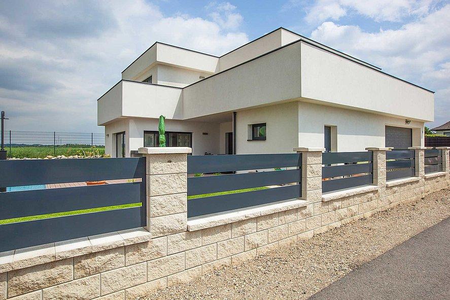 moderner Zaun mit breiten Querlatten in anthrazit auf Sockeln aus Steinziegeln vor einem Architektenhaus